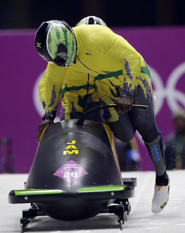 The team from Jamaica JAM-1, piloted by Winston Watts and brakeman Marvin Dixon, start their first run during the men's two-man bobsled competition at the 2014 Winter Olympics, Sunday, Feb. 16, 2014, in Krasnaya Polyana, Russia. (AP Photo/Dita Alangkara)