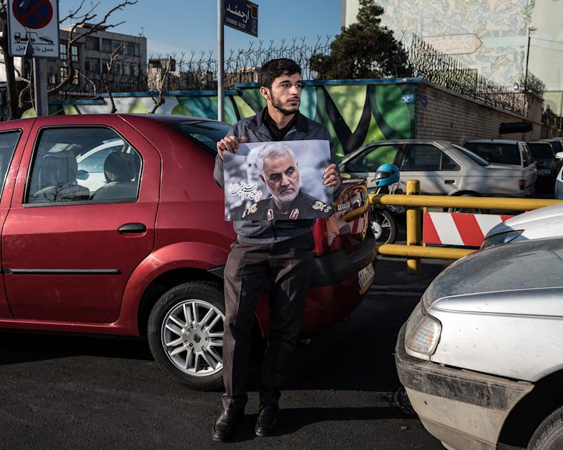 A man holds a poster of Soleimani in traffic in Tehran. | Newsha Tavakolian—Magnum Photos for TIME