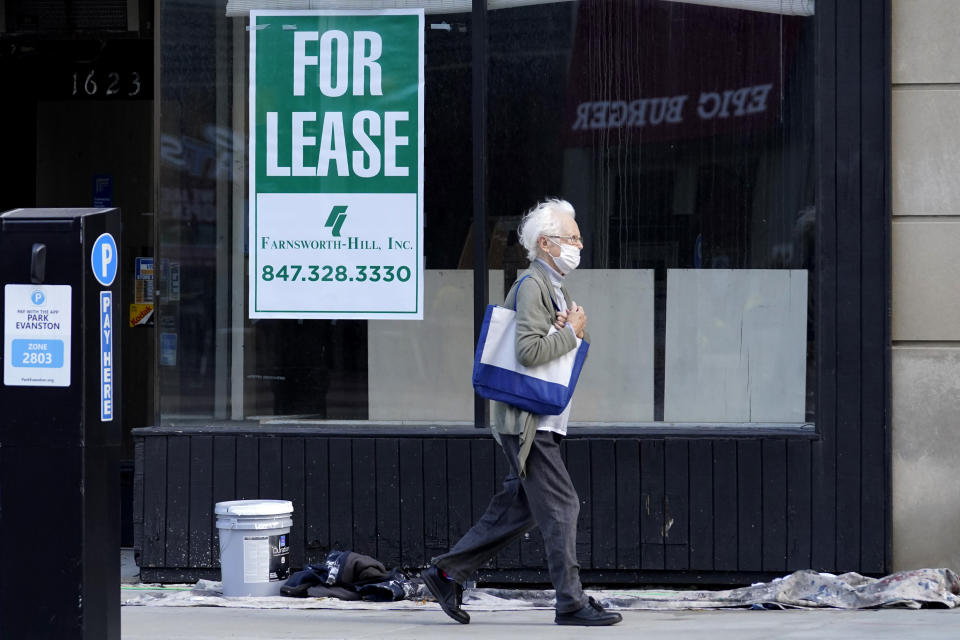 """FILE - In this Nov. 6, 2020, file photo, a man walks past an empty store with a """"For Lease"""" sign in downtown Evanston, Ill. States in the U.S. are renewing their push for more federal money to deal with the fallout from the coronavirus outbreak and to help them distribute a vaccine when one becomes widely available sometime in 2021. (AP Photo/Nam Y. Huh, File)"""