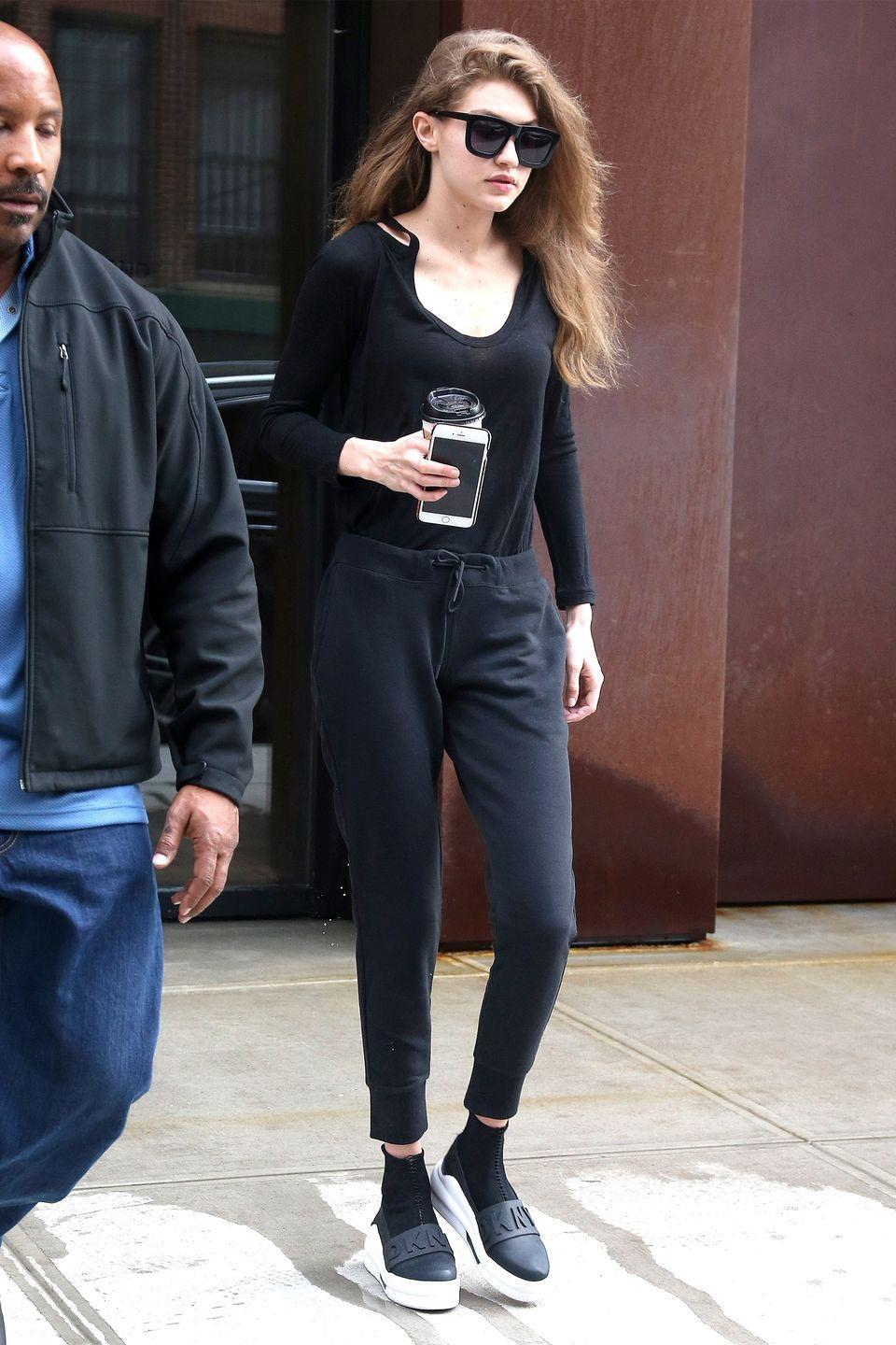 <p>In a black scoop neck shirt tucked into navy jogger sweatpants with DKNY sneakers and Karen Walker Eyewear while out in New York City. </p>