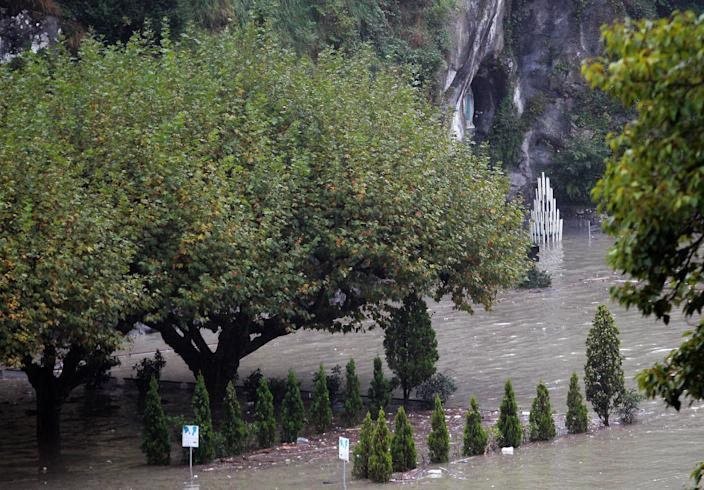 A guardian of Lourdes sanctuary looks the Grotto of Lourdes flooded, in Lourdes, southwestern France, Saturday, Oct. 20, 2012. French rescue services and police are evacuating hundreds of pilgrims from hotels threatened by floodwaters from a rain-swollen river in the Roman Catholic shrine town of Lourdes. (AP Photo/Bob Edme)