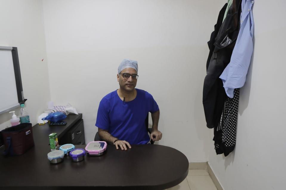 Dr. Kedar Toraskar, head of critical care, center, sits down for a quick lunch in the doctors room at the Mumbai Central Wockhardt Hospital in Mumbai, India, June 4, 2021. The recent coronavirus surge in India affected young people on a scale his team of critical care doctors hadn't previously seen. Toraskar and his team of ICU doctors are still drained from the incredibly challenging last few months. (AP Photo/Rajanish Kakade)