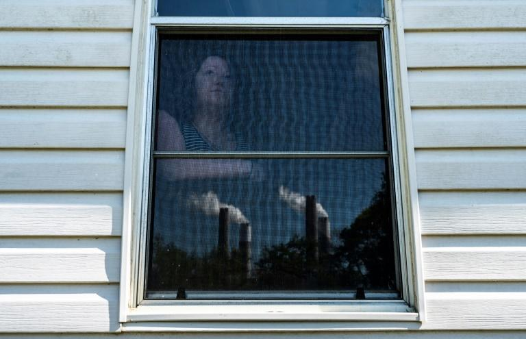 Jacey Maharrey, 27, poses for a photo as she looks at steam and exhaust from the Miller coal plant near her home in Alabama
