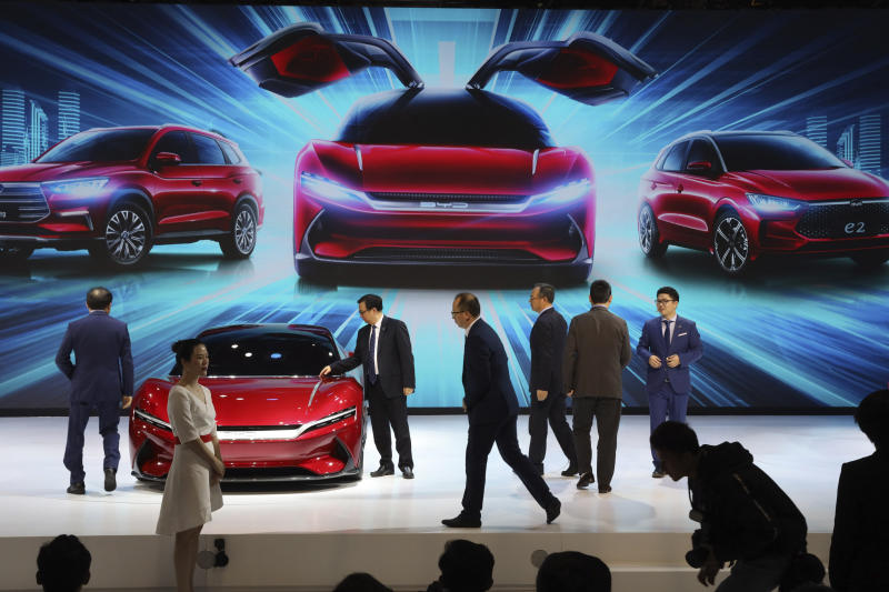 In this April 16, 2019, photo, attendees take a close look at cars from BYD at the Auto Shanghai 2019 show in Shanghai. China's electric car sales are stalling following the end of multibillion-dollar subsidies that made it the biggest market for the technology. Communist leaders want to make China a leader in electric cars but are shifting the burden to the industry by imposing mandatory sales quotas (AP Photo/Ng Han Guan)