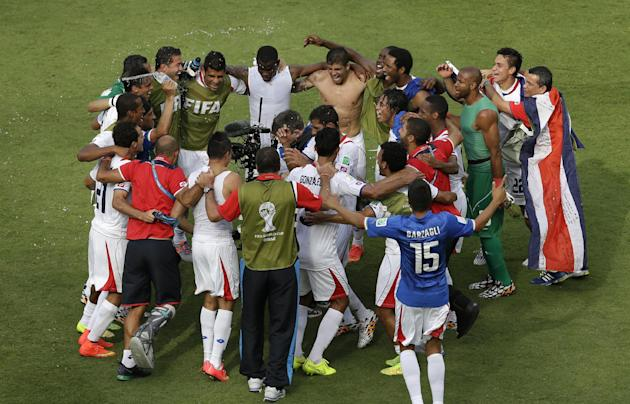 Costa Rica players celebrate after beating Italy. (Hassan Ammar/AP Photo)
