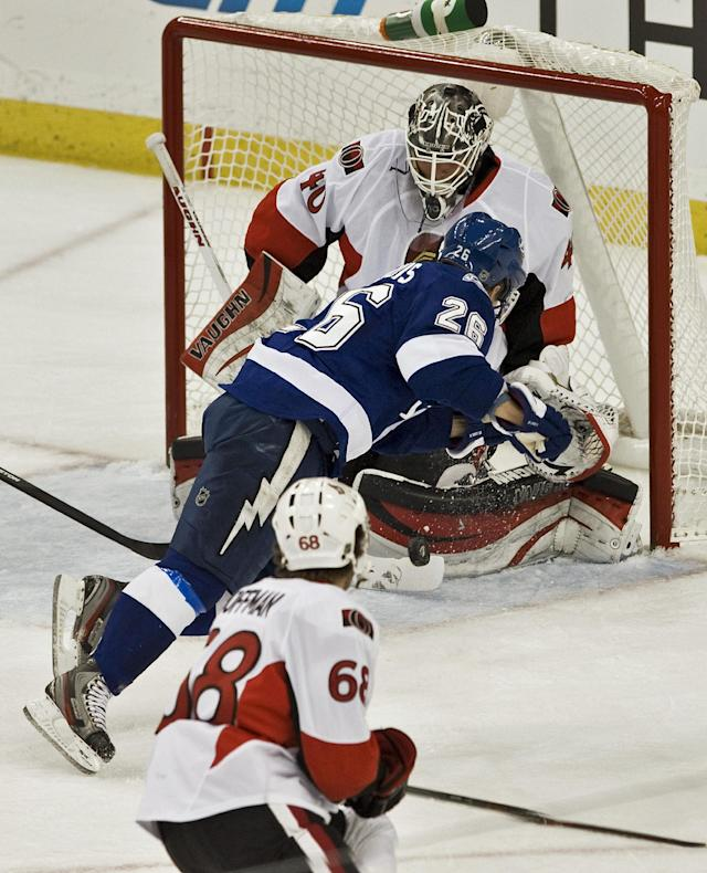 Ottawa Senators' Mike Hoffman (68) looks on as Tampa Bay Lightning's Martin St. Louis (26) scores on Senators goalie Robin Lehner (40) during the first period of an NHL hockey game on Thursday, Dec. 5, 2013, in Tampa, Fla. (AP Photo/Steve Nesius)