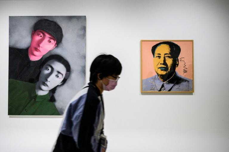 Work on display at the Hong Kong Museum of Art exhibition include a piece by Chinese painter Zhang Xiaogang (L) and a silkscreen of 'Portrait of Chairman Mao Zedong' by US artist Andy Warhol