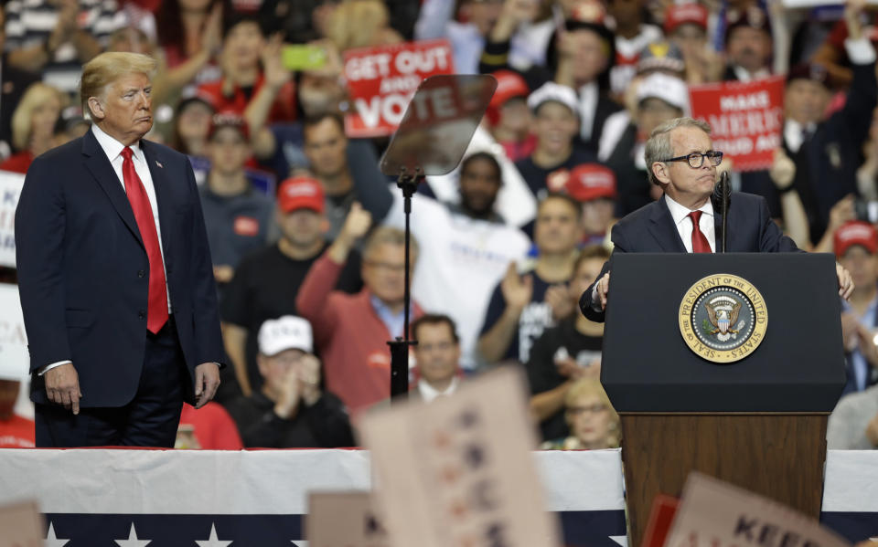 FILE-This Monday, Nov. 5, 2018 file photo shows President Donald Trump listening as Ohio gubernatorial candidate Mike DeWine speaks at a campaign rally, in Cleveland. DeWine on Monday Nov. 16, 2020 found himself on the receiving end of criticism by President Donald Trump and praise by President-Elect Joe Biden with a focus on the 2022 elections. Trump on Monday appeared to suggest in a tweet that DeWine needed a primary challenger. (AP Photo/Tony Dejak, File)