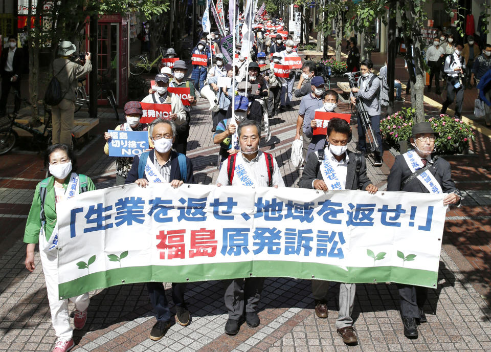 "A group of plaintiffs and supporters march ahead of the Sendai High Court's ruling on the Fukushima Dai-ichi nuclear plant disaster in Sendai, northern Japan, Wednesday, Sept. 30, 2020. The court on Wednesday found negligence by the government and the operator of the wrecked Fukushima nuclear plant in failing to take tsunami measures to prevent the 2011 nuclear disaster, ordering them to jointly pay some 1 billion yen ($9.5 million) in damages to thousands of residents for their lost livelihoods. The banner reads: ""Return jobs, return regions!"" (Kyodo News via AP)"
