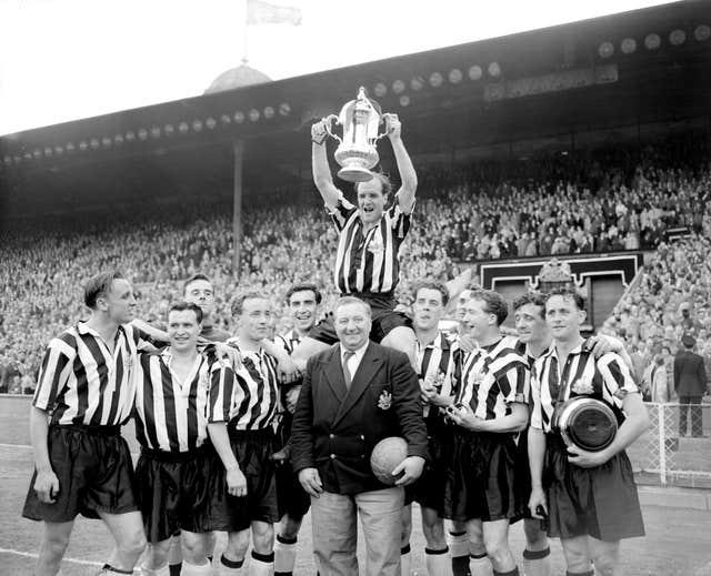 Newcastle captain Jimmy Scoular lifts the FA Cup aloft after a 3-1 victory over Manchester City in the 1955 final