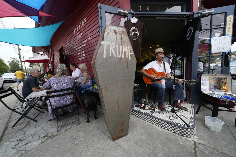 Folk musician Ted Hefko performs next to a mock casket with the name Trump written on it, as patrons dine at the Bywater Bakery in New Orleans, Saturday, Nov. 7, 2020, just an hour after news outlets called the Presidential election. Democrat Joe Biden defeated President Donald Trump to become the 46th president of the United States on Saturday, positioning himself to lead a nation gripped by the historic pandemic and a confluence of economic and social turmoil. (AP Photo/Gerald Herbert)