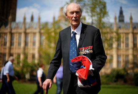 FILE PHOTO: World War Two Norwegian resistance fighter Joachim Roenneberg holds a Union flag presented to him at the House of Lords in Westminster, London