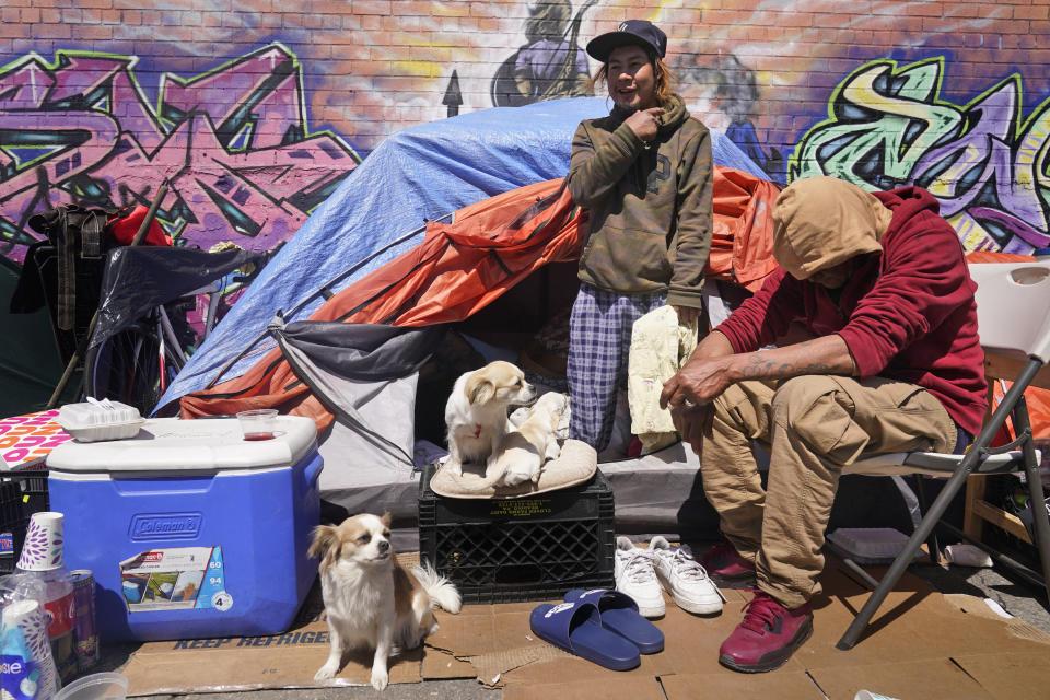 Lucio Lopez, left, talks with friends as he stands in a tent that is part of a homeless encampment in the Queens borough of New York, Tuesday, April 13, 2021. Unemployment among Hispanic immigrants has doubled in the U.S., going from 4.8% in January 2020 to 8.8% in February 2021, according to the Migration Policy Institute. These numbers don't take into consideration immigration status but activists and social workers in states like New York or California say more vulnerable immigrants, whom often don't qualify for aid, are finding themselves without a home. (AP Photo/Seth Wenig)