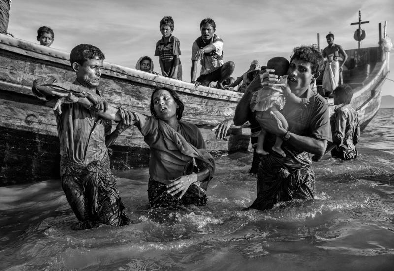 A Rohingya refugee woman is helped from a boat as she arrives exhausted on the Bangladesh side of the Naf River after fleeing her village in Myanmar. (Kevin Frayer via Getty Images)