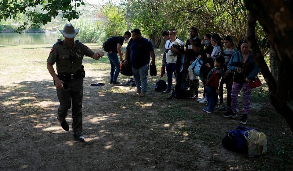 FILE - In this June 16, 2021 file photo, Texas Department of Public Safety officers work with a group of migrants who crossed the border and turned themselves in Del Rio, Texas. Republican Texas Gov. Greg Abbott's newest immigration crackdown, allowing state troopers to pull over vehicles suspected of carrying migrants on the basis that they could increase the spread of COVID-19 in the U.S., brought swift backlash from the Justice Department as criticism of the order mounted.