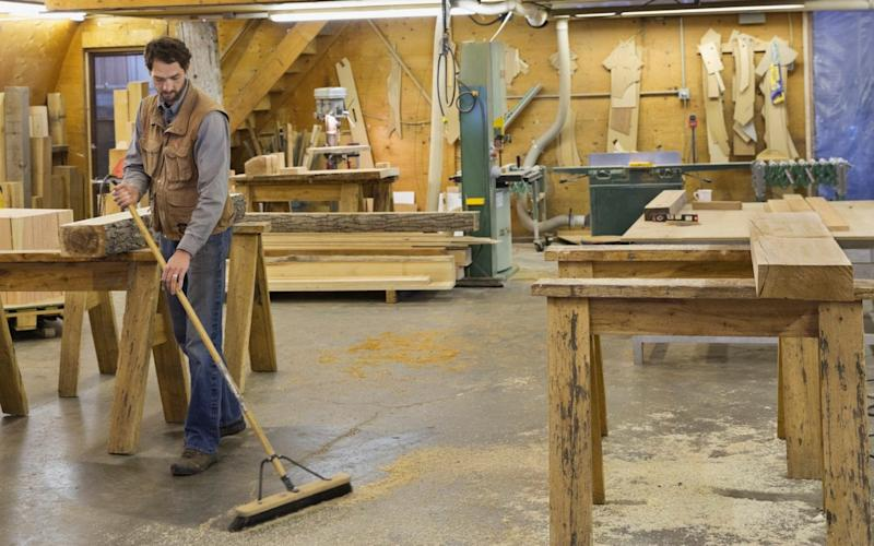 Furniture maker told to stop sweeping up wood dust from his factory floor with a broom by concerned health and safety bosses - Hero Images