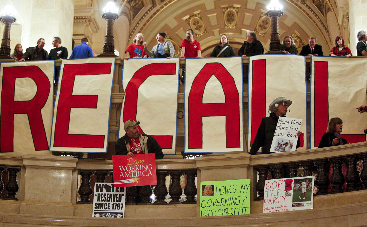 FILE - In this Jan 25, 2012 file photo, protestors show off signs in the rotunda of the State Capitol Wisconsin prior to Gov. Scott Walker's state of the state address in Madison, Wis. More than a year after the standoff over union rights that rocked Wisconsin and the nation for weeks, the Republican Governor will face Milwaukee's Democratic Mayor Tom Barrett in Tuesday's recall election. (AP Photo/Andy Manis)