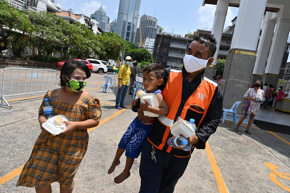 A motorcycle taxi driver, wearing a face mask as a preventive measure against the spread of the COVID-19 novel coronavirus, carries a boy after receiving food donations organised by the Holy Redeemer Catholic Church in Bangkok on May 6, 2020. (Photo by Romeo GACAD / AFP) (Photo by ROMEO GACAD/AFP via Getty Images)