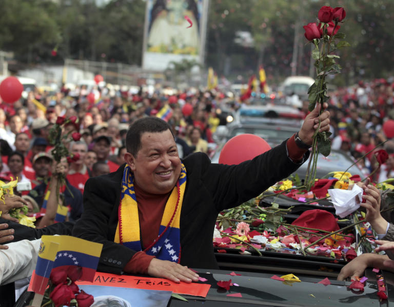 Venezuela's President Hugo Chavez holds up flowers thrown by supporters during his caravan from Miraflores presidential palace to the airport in Caracas, Venezuela, Friday Feb. 24, 2012. Chavez bid an emotional goodbye to soldiers and supporters and waved to crowded streets in Caracas on his way to Cuba for urgent surgery to remove a tumor he says is probably malignant. (AP Photo/Fernando Llano)