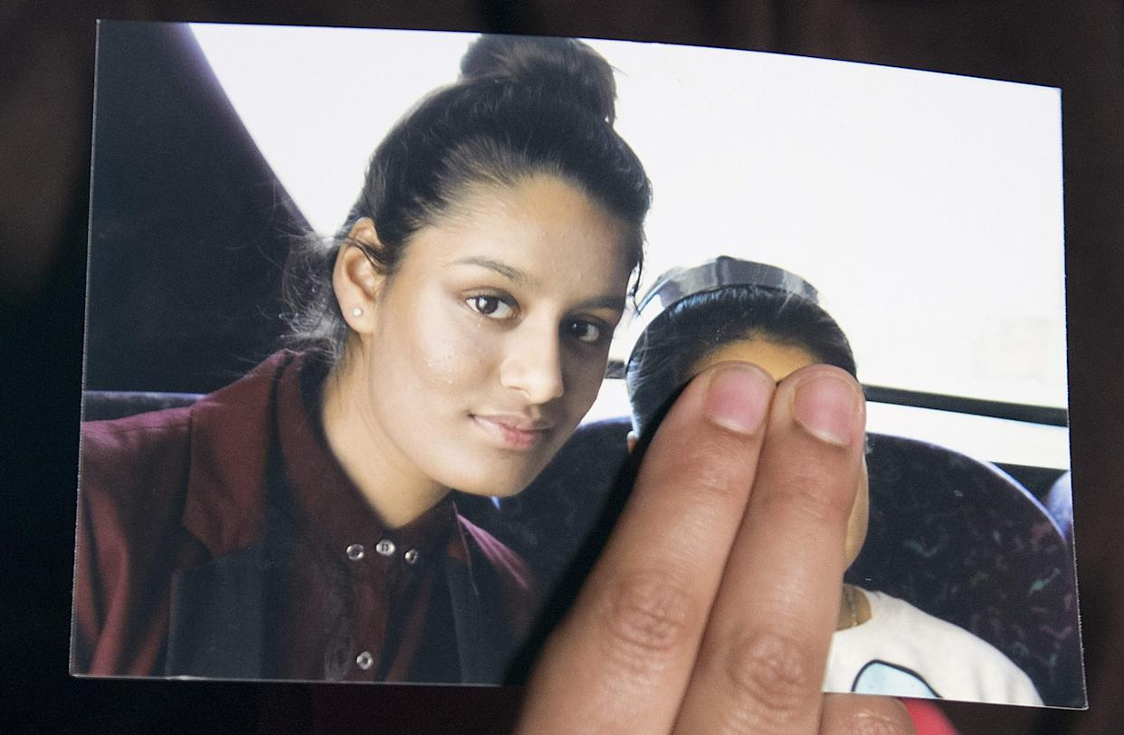 A family member of Shamima Begum holds a picture of the British girl, left, while being interviewed by the media in London, on February 22, 2015.