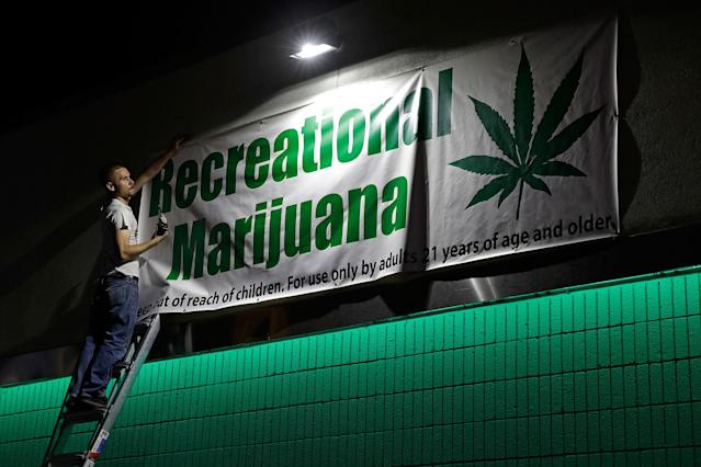 <p>Bryce Tallitsch hangs up a sign for recreational marijuana at the NuLeaf dispensary, Friday, June 30, 2017, in Las Vegas, Nev. (Photo: John Locher/AP) </p>