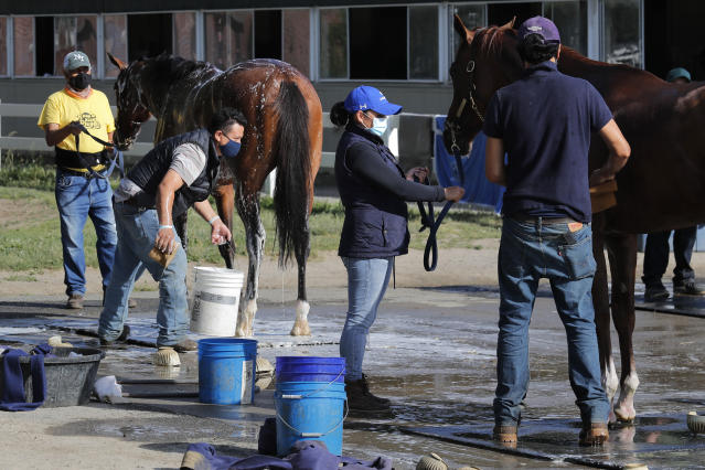 Grooms bathe horses while wearing masks at Belmont Park in Elmont, N.Y., Wednesday, June 17, 2020. The 152nd running of the Belmont Stakes is scheduled to be run on Saturday. (AP Photo/Seth Wenig)