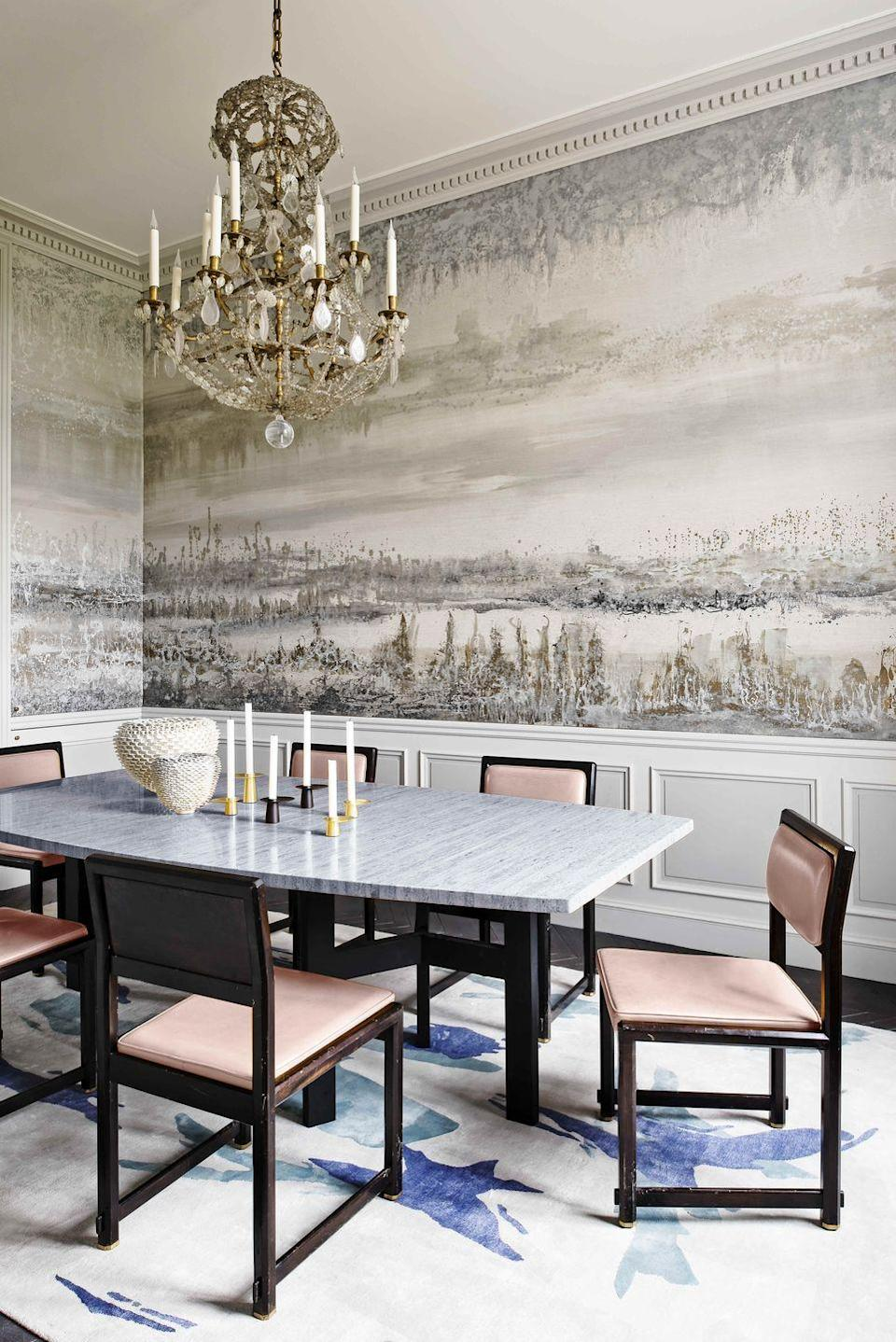 """<p>Within the dining room of this <a href=""""https://www.veranda.com/home-decorators/a30145127/jean-louis-deniot-paris-flat/"""" rel=""""nofollow noopener"""" target=""""_blank"""" data-ylk=""""slk:18th-century Paris apartment"""" class=""""link rapid-noclick-resp"""">18th-century Paris apartment</a>, a grisaille and metallic mural by <a href=""""http://www.florencegirette.com"""" rel=""""nofollow noopener"""" target=""""_blank"""" data-ylk=""""slk:Florence Girette"""" class=""""link rapid-noclick-resp"""">Florence Girette</a> envelopes the entire room, echoing the glimmering lights from the Tuileries outside. To bring color back into the monochromatic space, designer <a href=""""https://www.deniot.com"""" rel=""""nofollow noopener"""" target=""""_blank"""" data-ylk=""""slk:Jean-Louis Deniot"""" class=""""link rapid-noclick-resp"""">Jean-Louis Deniot</a> laid down a rug dressed with brilliant blue tones from <a href=""""https://www.diurne.com/en/gallery/"""" rel=""""nofollow noopener"""" target=""""_blank"""" data-ylk=""""slk:Galerie Diurne"""" class=""""link rapid-noclick-resp"""">Galerie Diurne</a>. Both the pink chairs and dining table are vintage. </p>"""