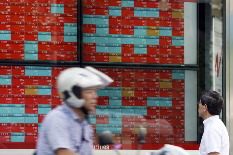 A man looks at an electronic stock board showing Japan's Nikkei 225 index at a securities firm in Tokyo Thursday, Sept. 12, 2019. Asian shares were mixed Thursday after China moved to ease trade tensions. (AP Photo/Eugene Hoshiko)