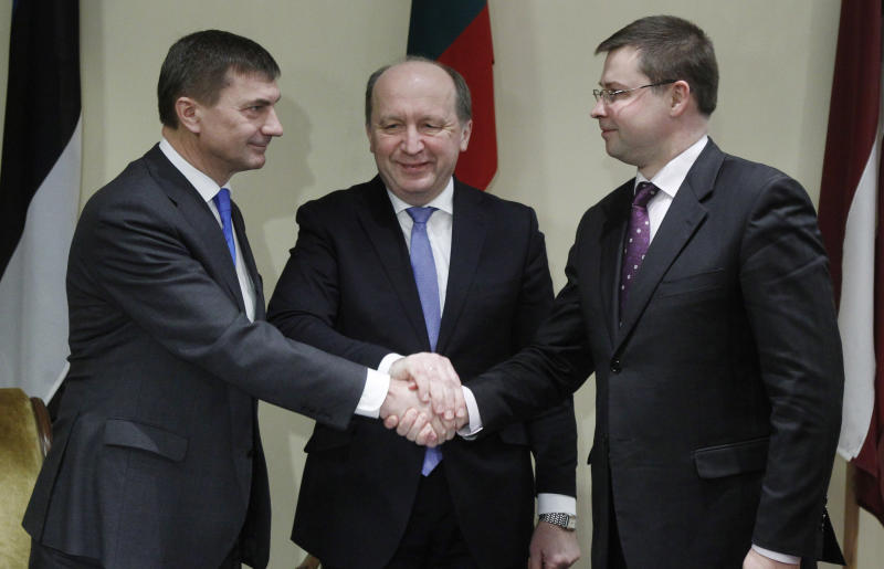 Latvia's Prime Minister Valdis Dombrovskis, right, Estonia's Prime Minister Andrus Ansip, left, and Lithuania's Prime Minister Andrius Kubilius shake hands during the Baltic Prime Ministers meeting in Vazgaikiemio village, Prienai district some 125 kilometers (77.5 miles) from Vilnius, Lithuania, Thursday, March 8, 2012. The meeting may outline how each Baltic country will contribute to a future nuclear power plant, planned to be construct at Ignalina, Lithuania. (AP Photo/Mindaugas Kulbis)