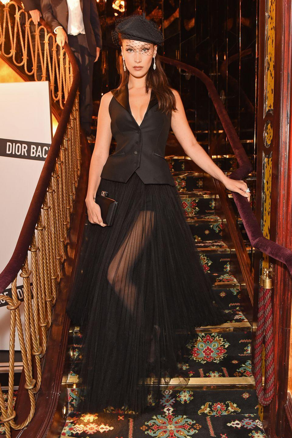 <p>In a black beret with a fishnet veil, satin vest, sheer ball skirt, black clutch, and diamond dangling earrings while attending the Dior Backstage launch party in London.</p>