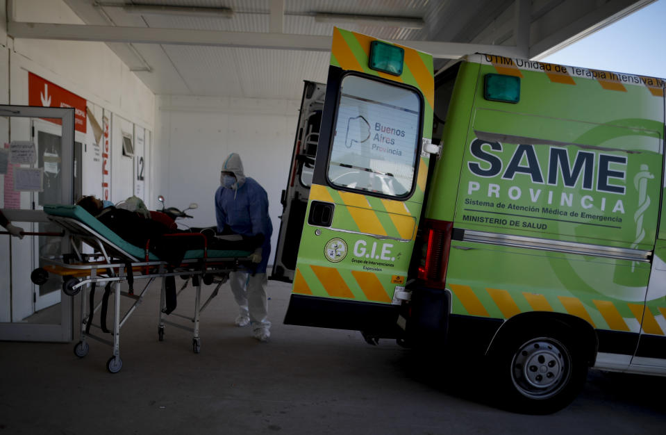 Health workers bring in a patient on a stretcher to a COVID-19 hospital in Mar del Plata, Argentina, Saturday, Oct. 10, 2020. Mar del Plata has become an epicenter in a coronavirus surge through Argentina's interior that has given it the fifth-highest confirmed case total in the world. (AP Photo/Natacha Pisarenko)