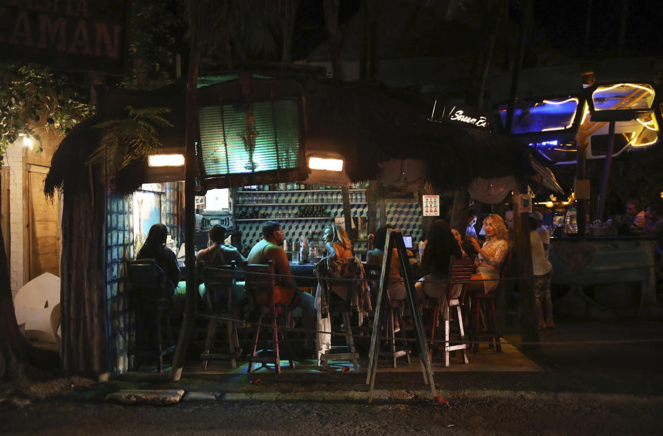 Tourists chat at a local bar on the main tourist strip of Tulum, Quintana Roo state, Mexico, Monday, Jan. 4, 2021. More U.S. tourists came to Quintana Roo during this pandemic-stricken holiday season than did a year earlier when the world was just beginning to learn of the coronavirus. They account for 9 out of 10 foreign tourists, said state Tourism Secretary Marisol Vanegas. (AP Photo/Emilio Espejel)