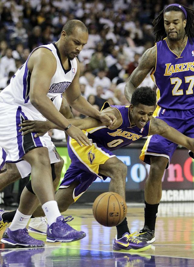 Sacramento Kings forward, Chuck Hayes, left, Los Angeles Lakers guard Nick Young, center, scrambles after a loose ball as Lakers forward Jordan Hill, right, stands by during the first quarter of an NBA basketball game in Sacramento, Calif., Friday, Dec. 6, 2013. (AP Photo/Rich Pedroncelli)