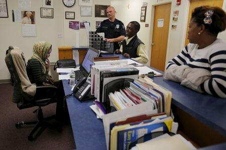 Lewiston Police Officer Patrick Griffin (top C), a community resource officer, talks to workers at the Maine Immigrant and Refugee Services facility in Lewiston, Maine June 1, 2015.  REUTERS/Brian Snyder -