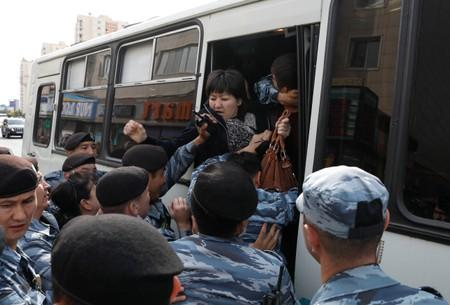 Kazakh law enforcement officers detain a woman during a rally held by opposition supporters in Nur-Sultan