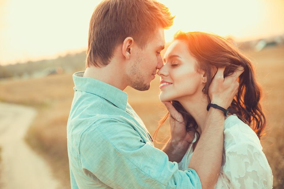 Man and woman about to kiss in field at sunset
