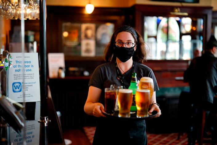 A member of bar staff wearing a face mask carries drinks inside the Wetherspoon pub, Goldengrove in Stratford in east London, on July 4. (Photo: TOLGA AKMEN via Getty Images)