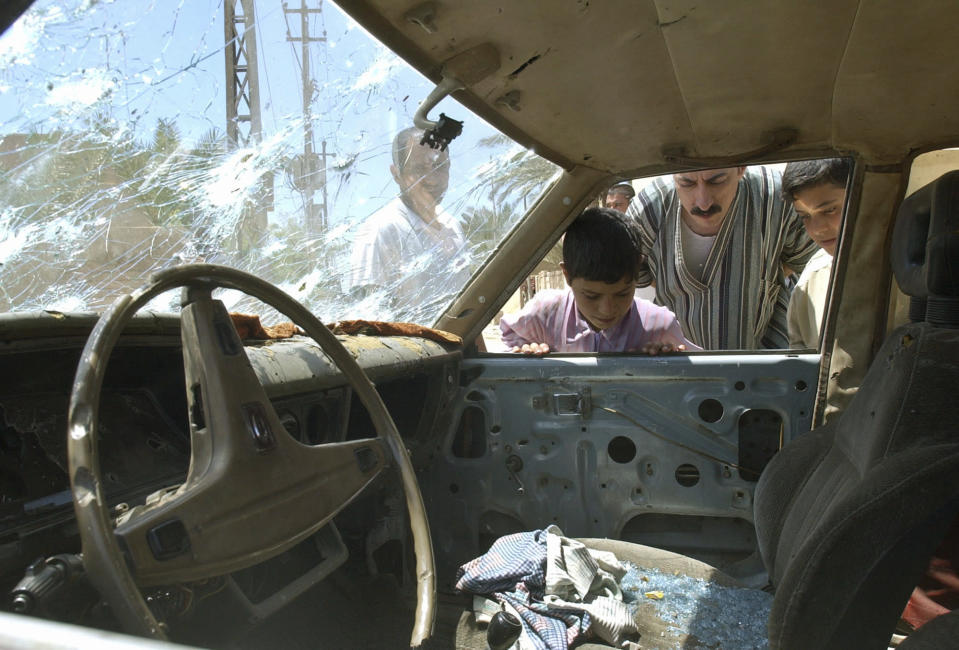FILE - In this April 29, 2003, file photo, residents of Fallujah, Iraq look into a bullet riddled car outside a school where U.S. soldiers fired on demonstrators the night before. The U.S. launched its invasion of Iraq on March 20, 2003, unleashing a war that led to an insurgency, sectarian violence and tens of thousands of deaths. (AP Photo/Ali Haider, File)