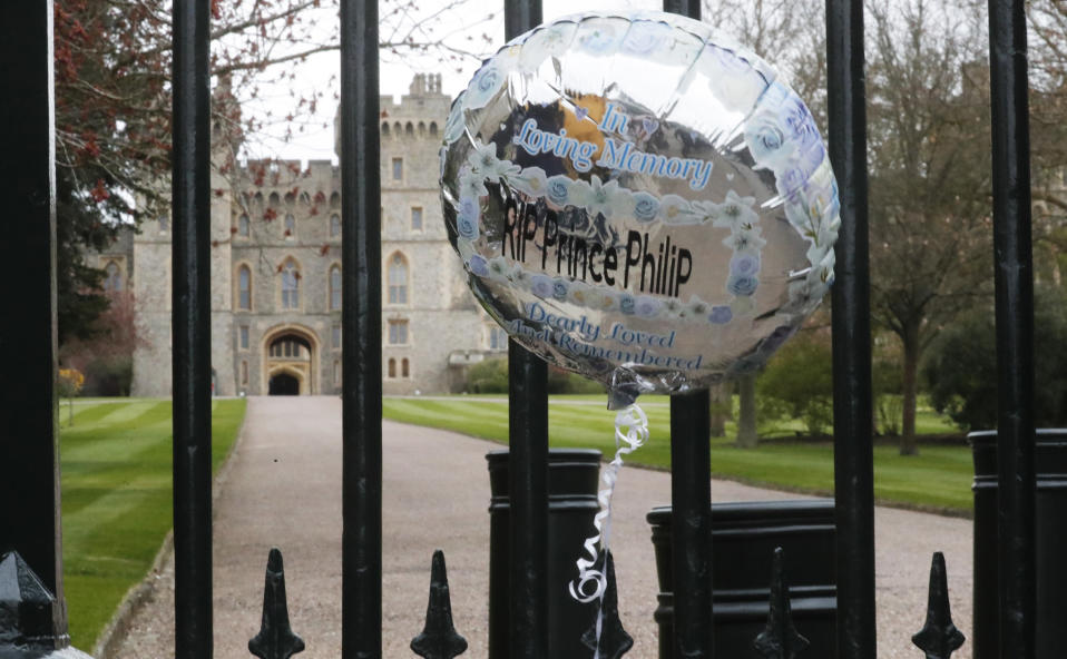 A balloon left by a member of the public hangs outside the gates of Windsor Castle, a day after the death of Britain's Prince Philip, in Windsor, England, Saturday, April 10, 2021. Britain's Prince Philip, the irascible and tough-minded husband of Queen Elizabeth II who spent more than seven decades supporting his wife in a role that mostly defined his life, died on Friday. (AP Photo/Frank Augstein)