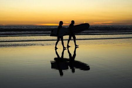 Surfers walk out of the Pacific Ocean on Venice Beach in Los Angeles
