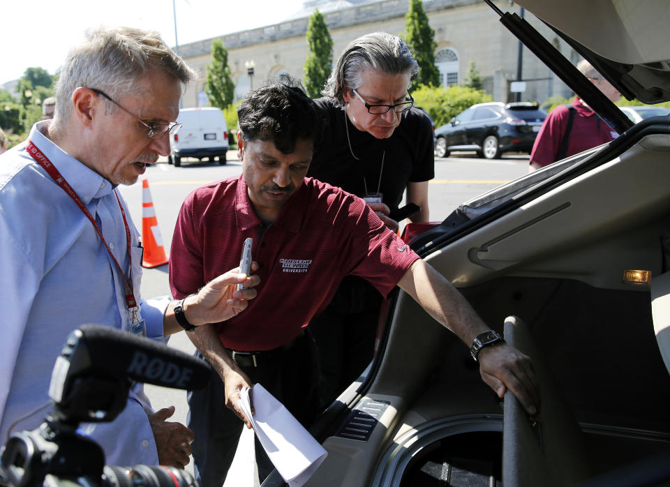 Carnegie Mellon University Professor Raj Rajkumar (C) explains the workings of the university's autonomous car in Washington June 24, 2014. The 2011 Cadillac SRX is able to control steering, speed and braking in harmony with the autonomous systems (radar, lidar and infrared sensors) that detect and avoid obstacles in the road. REUTERS/Gary Cameron (UNITED STATES - Tags: POLITICS TRANSPORT SCIENCE TECHNOLOGY BUSINESS)