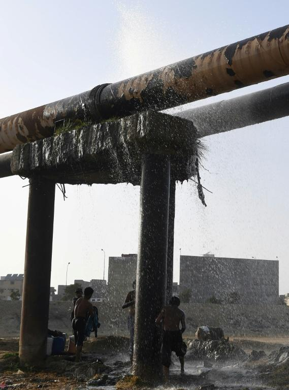 Karachi youngsters cool off under a leaking water pipeline