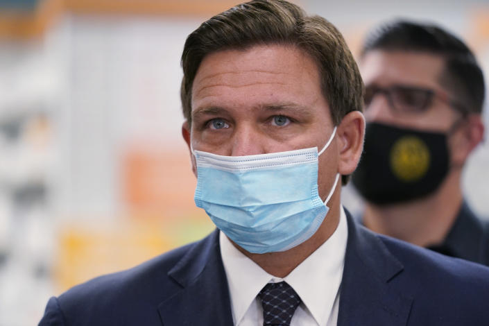 Wearing a mask to prevent the spread of COVID-19, Florida Gov. Ron DeSantis looks on during a news conference, Tuesday, Feb. 23, 2021, at a Navarro Discount Pharmacy in Hialeah, Fla. DeSantis announced that seniors will soon be able to receive COVID-19 vaccinations at Navarro Discount Pharmacies and CVS y mas pharmacies in Miami-Dade County. (AP Photo/Wilfredo Lee)