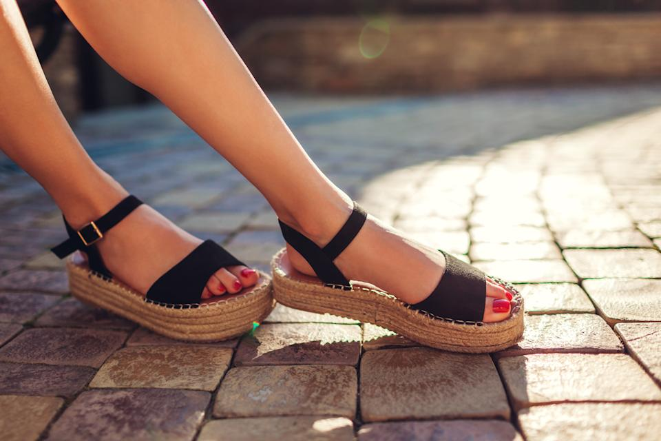 Stylish woman wearing black summer shoes with straw sole outdoors. Comfortable sandals. Beauty fashion. Footwear for Black friday sale