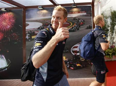 Red Bull Formula One driver Sebastian Vettel of Germany shows a thumbs up as he arrives ahead of the first practice session of the Singapore F1 Grand Prix at the Marina Bay street circuit in Singapore September 20, 2013. REUTERS/Edgar Su