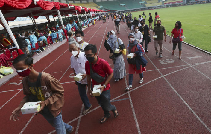People leave the Patriot Candrabhaga Stadium, with box of snack given to them after receiving a shot of the Sinovac vaccine for COVID-19 during a vaccination campaign in Bekasi on the outskirts of Jakarta, Indonesia, Thursday, July 1, 2021. (AP Photo/Achmad Ibrahim)