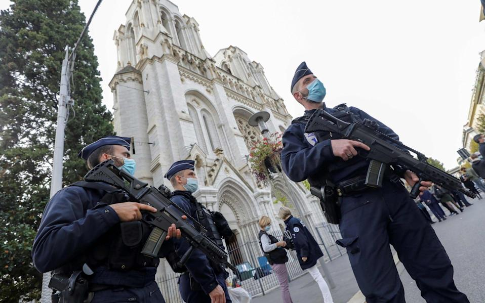 Police officers stand guard by the Notre-Dame Basilica in Nice - AFP
