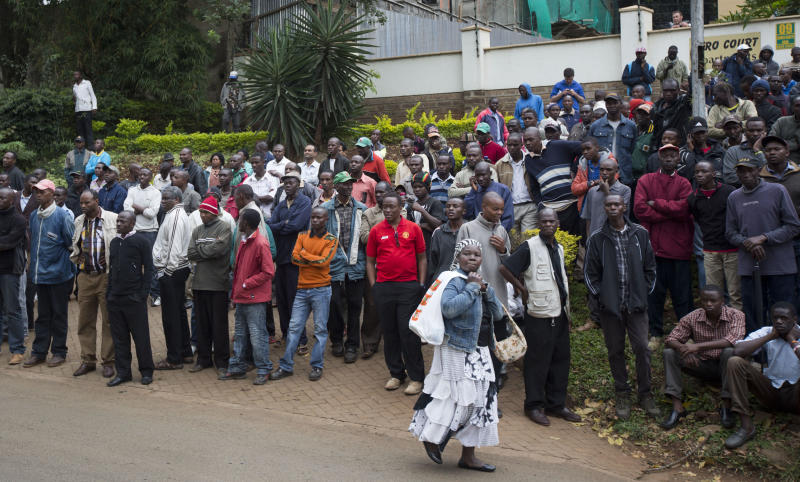 Groups of onlookers gather on a road looking down over the Westgate Mall in Nairobi, Kenya Sunday, Sept. 22, 2013. Multiple barrages of gunfire erupted Sunday morning from the upscale Kenyan mall where there is a hostage standoff with Islamic extremists nearly 24 hours after they attacked using grenades and assault rifles. (AP Photo/Ben Curtis)