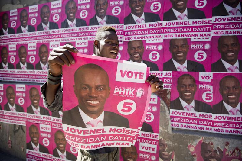 A supporter of presidential candidate Jovenel Moise holds up a campaign poster as he celebrates his candidate's victory in Petion-Ville, Haiti, Tuesday, Jan. 3, 2017. An electoral tribunal certified on Tuesday the presidential election victory of the first-time candidate. He will be sworn in on Feb. 7. (AP Photo/Dieu Nalio Chery)