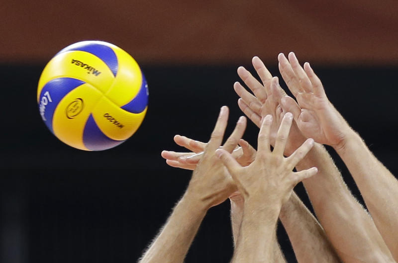 Volleyball players go for the ball during an exhibition match at Earls Court, site of the Olympic men's and women's volleyball competition, before the start of the 2012 Summer Olympics, Friday, July 27, 2012, in London. (AP Photo/Chris O'Meara)